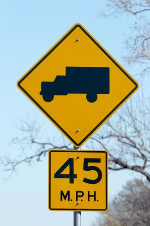 Sign warning that trucks frequently get on the highway ahead