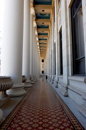 Hallway with ornate ceiling, floor, and pillars