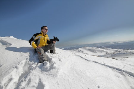 Man posing on mountain with camera photo