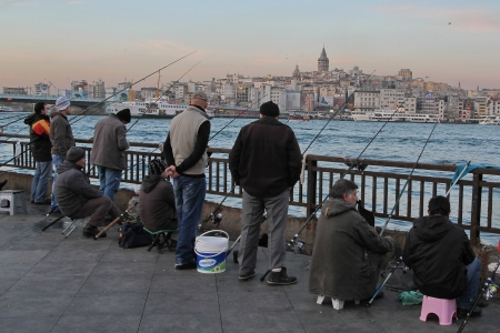 ISTANBUL, TURKEY - December 06: Men fishing on the Galata Bridge at evening with the Galata Tower in the background on the hill on 06 December 2012 in Istanbul