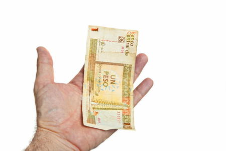 pesos: Male hand holding one Cuban Pesos bill isolated on white background