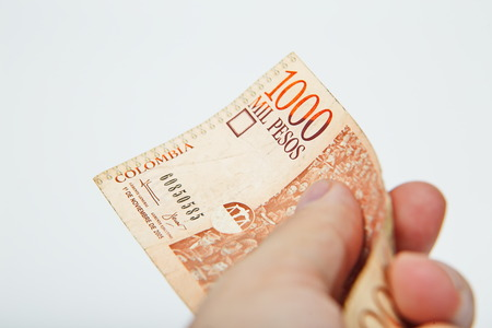 pay money: Male hand holding National currency of Colombia