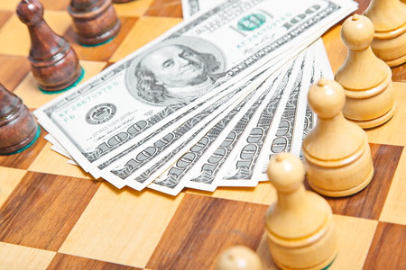 conquest: US dollars and chess figures on an old wooden chessboard