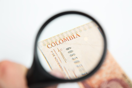 pesos: Magnifying Glass on the Colombian Pesos. Stock Photo