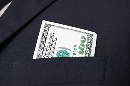 United States dollar (USD) bills - in businessman suit pocket Stock Photo