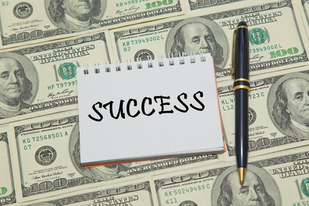 archival: Notebook page with text SUCCESS on dollar background Stock Photo