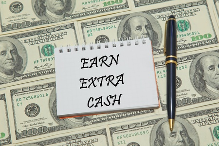 archival: Notebook page with text EARN EXTRA CASH on dollar background Stock Photo