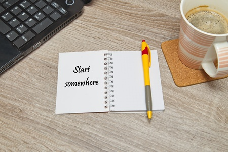 somewhere: Open notebook with Text Start Somewhere and a cup of coffee on wooden background Stock Photo