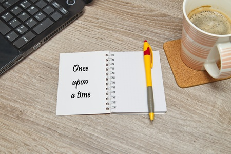 just in time: Open notebook with text Once upon a time and a cup of coffee on wooden background.
