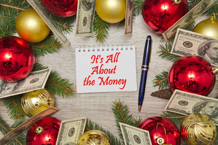 Christmas decoration with dollars and text in notebook ITS ALL ABOUT THE MONEY on wooden table Stock Photo