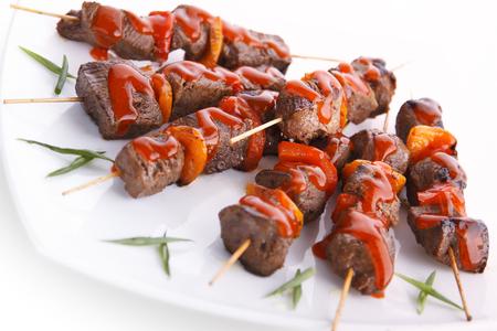 shashlik: Grilled juicy skewered shashlik on a plate with ketchup. Stock Photo