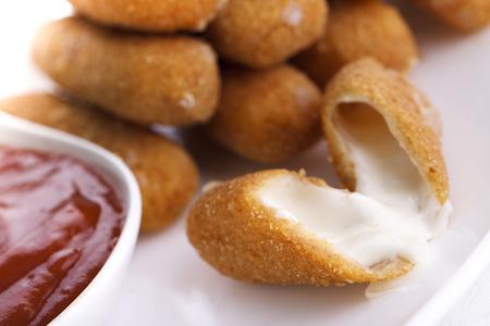 high calorie foods: Delicious mozzarella fried sticks with tomato sauce on white background