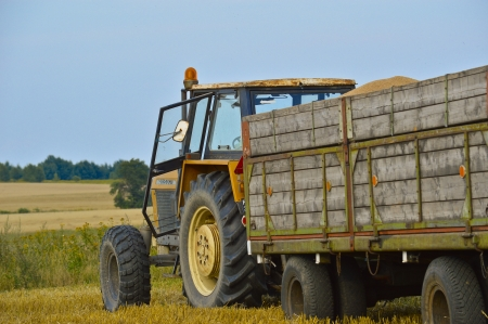 Tractor in a field with a trailer photo