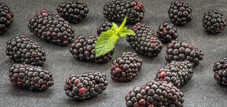 Tasty ripe blackberries on grey table, closeup. Organic dewberries. Raw brambles. Yummy seasonal fruits. Delicious vegan treat