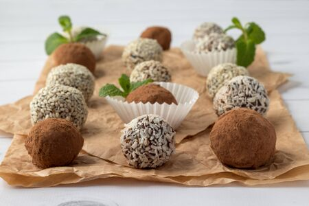 Energy bites with cocoa powder, sesame seeds and coconut flakes on parchment. Bliss balls with dried fruits on white wooden table. Vegan dessert recipe. Healthy snack Imagens