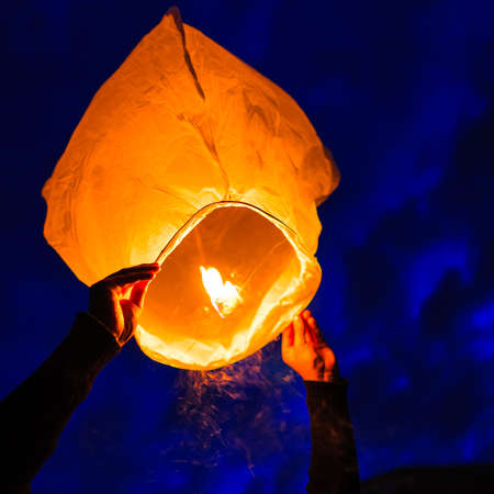 chinese lantern: Man holds a chinese lantern as it begins to float, England