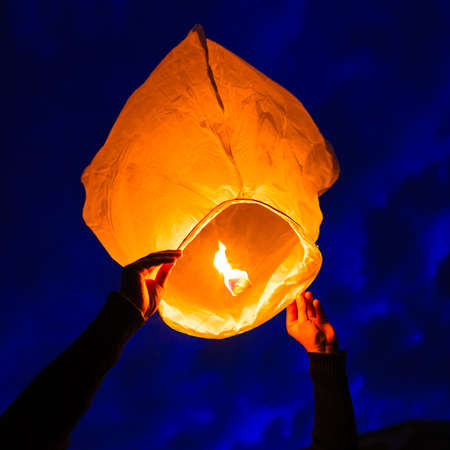 chinese lantern: Man holds a chinese lantern as it begins to float, England.