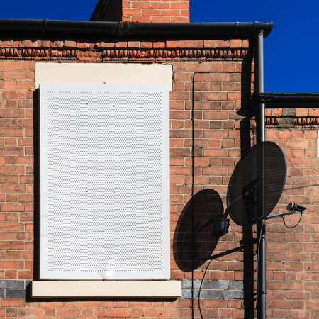 boarded up: Satellite dish and boarded up window, terrace house Stock Photo