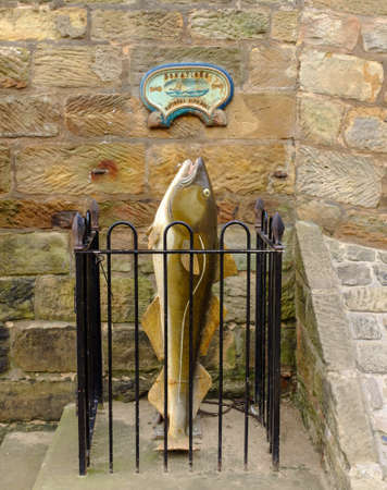 vertical format: ROBIN HOODS BAY, ENGLAND - SEPTEMBER 16TH: A plaque and plastic fish requesting donations for the National Life Boat Service. Robin Hoods Bay, England. 16th September 2014.