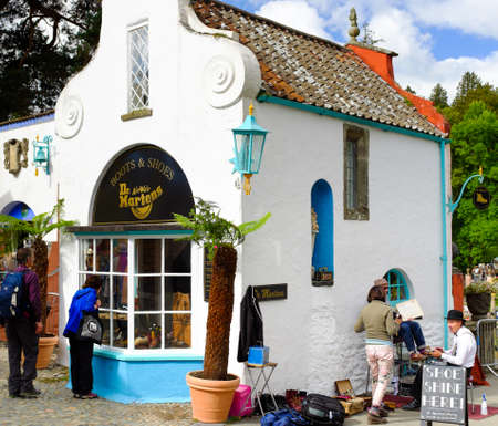 PORTMEIRION, NORTH WALES - SEPTEMBER 7TH: A man is shining a lady customers shoes at the Dr Martins shoe store on 7TH September 2014 in Portmeirion, North Wales, UK.