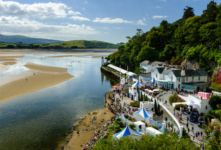 boarders: PORTMEIRION, NORTH WALES - SEPTEMBER 7TH: Paddle Boarders (courtesy of Volvo cars sponsorship) on the estuary. The Hotel Portmeirion to the right, on 7TH September 2014 in Portmeirion, North Wales, UK. Editorial