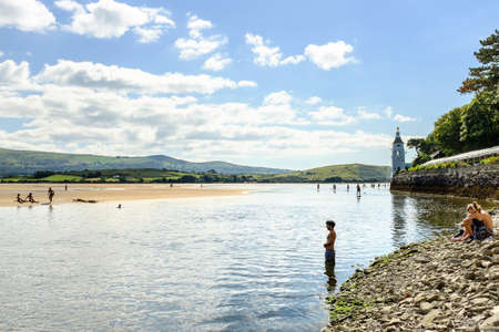 boarders: PORTMEIRION, NORTH WALES - SEPTEMBER 7TH: Man entering River Dwyryd, in the distance Paddle Boarders (courtesy of Volvo cars sponsorship) on the estuary, on 7TH September 2014 in Portmeirion, North Wales, UK.