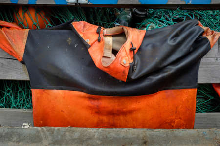 smock: SCARBOROUGH, ENGLAND - SEPTEMBER 2014: Fishermans waterproof oilskin smock jacket hung out to dry. 18th September 2014, in Scarborough fishing harbour, England.