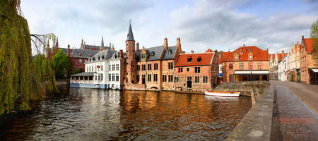 Panoramic view of the colorful buildings of Bruges Belgium reflecting on the canal water