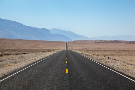 Endless and lonely blacktop road going disappearing into the Horizon on way to Death Valley National Park 版權商用圖片