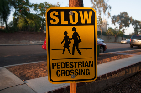 Sign says SLOW PEDESTRIAN CROSSING on the street of Los Angels, America. Street signs means the traffic rule, advertising, or many things.