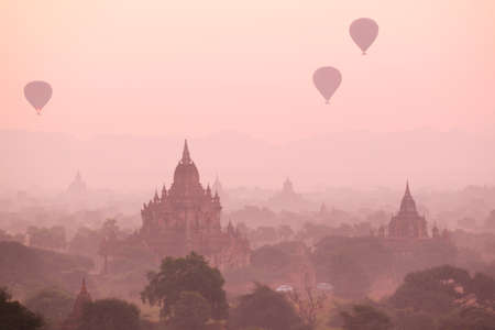 flew: In the morning mist rose, three hot-air balloons flew over the stupas. Bagan, Myanmar Stock Photo