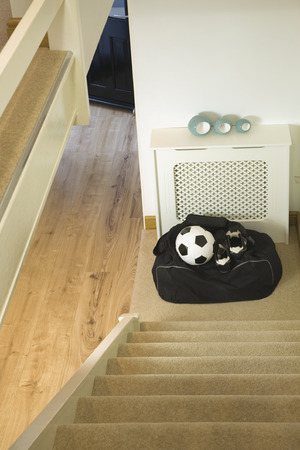 football boots: football kit bag,ball and football boots ready to take at the bottom of the home stairs