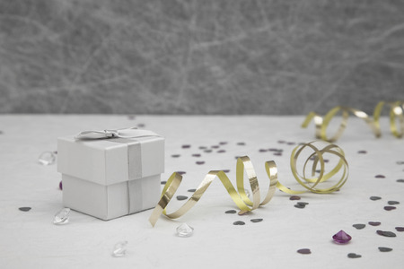table decorations: Wedding Favor box on a White tablecloth with gold ribbons, silver heart confetti and small diamond table decorations