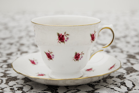 cup and saucer: Vintage tea cup, saucer and tablecloth Stock Photo
