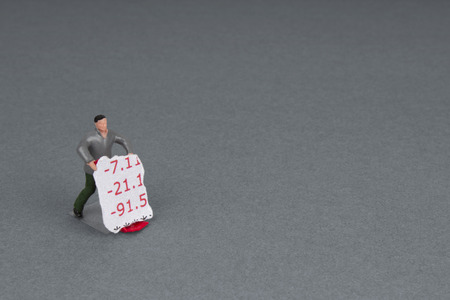 bank statement: plastic workman figurine with a torn section of bank statement on a trolley.