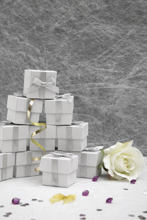 wedding favors: Wedding Favor boxes on a White tablecloth with gold ribbons, bows, silver heart confetti and small diamond table decorations Stock Photo