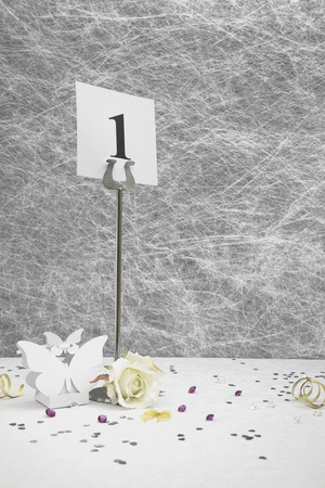 table decorations: Wedding table numbers and Favor box on a White tablecloth with ribbons, bows, heart confetti and diamond table decorations