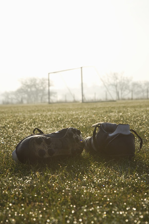 football pitch: football boots on a empty football pitch, frosty winter morning sunrise Stock Photo