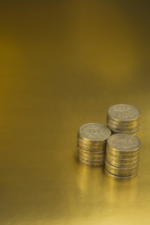 British One Pound Coins on a Gold background Imagens