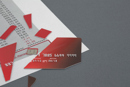 bank statement: Cut up Credit Card on top of a Bank Statement Stock Photo