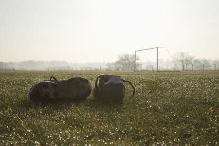 football pitch: football boots on a empty football pitch,frosty winter morning sunrise