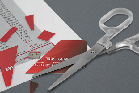 credit crunch: Cut up Credit Card and a pair Scissors on top of a Bank Statement