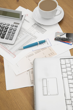 calculated: credit cards on a laptop with credit card statements a cup of hot coffee and calculator in the background Stock Photo
