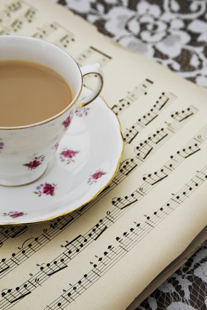 musical score: Vintage tea cup,saucer and Old Musical Score Sheets on a flora tablecloth Stock Photo