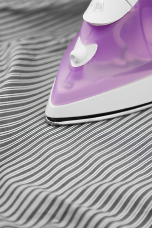 steam iron: Steam Iron on a stripe shirt Stock Photo