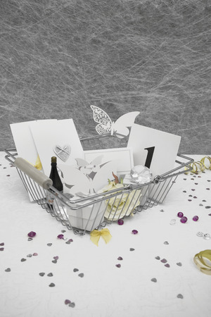 favors: Wedding Favors in a shopping basket on a White tablecloth with ribbons, bows, heart confetti and small diamond table decorations