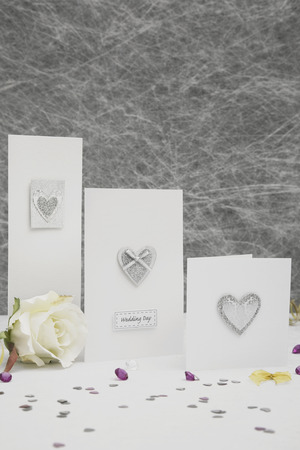 table decorations: Wedding congratulation cards on a White tablecloth with gold ribbons, bows, silver heart confetti and diamond table decorations
