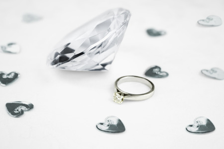 fake diamond: close up of a fake clear glass diamond  next to a wedding engagement ring Stock Photo