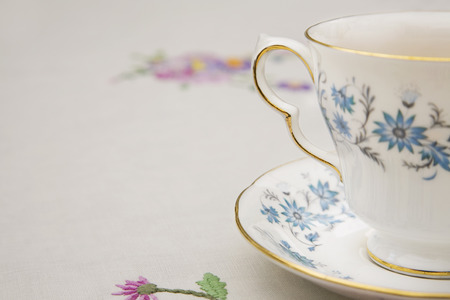 saucer: Vintage tea cup, saucer and tablecloth Stock Photo