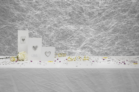Wedding congratulation cards on a White tablecloth with gold ribbons, bows, silver heart confetti and diamond table decorations